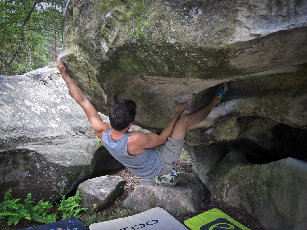 Peter working an awesome roof boulder at Les Béorlots, Fontainebleau