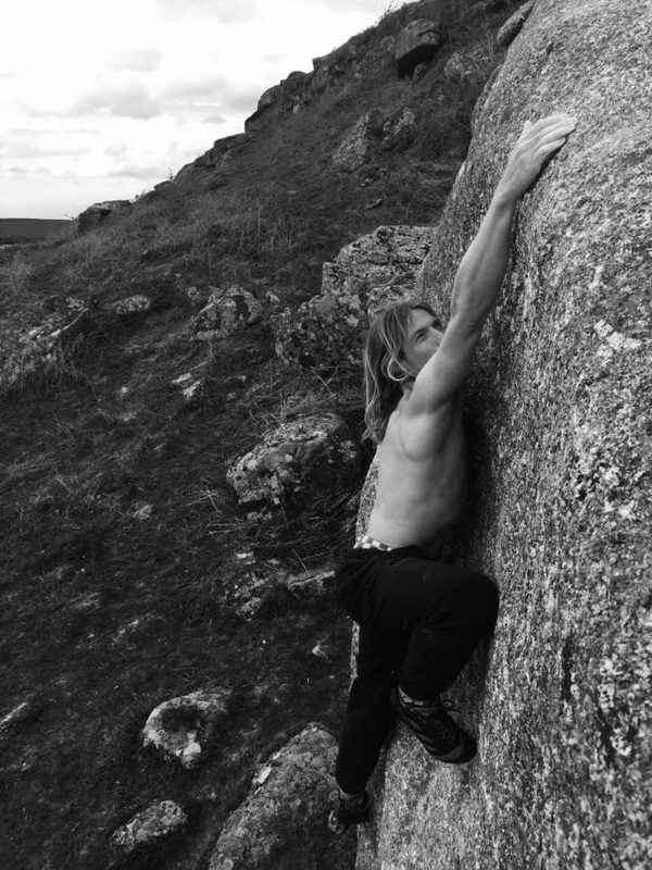 Matt Stokes climbing a highball sloper boulder at Helman Tor in black and white, GB bouldering