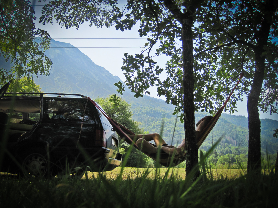 Man relaxing in a hammock in the shade, tied between a tree and a vw golf estate. Escaping the hot alpine sun in the valley of the mountains.