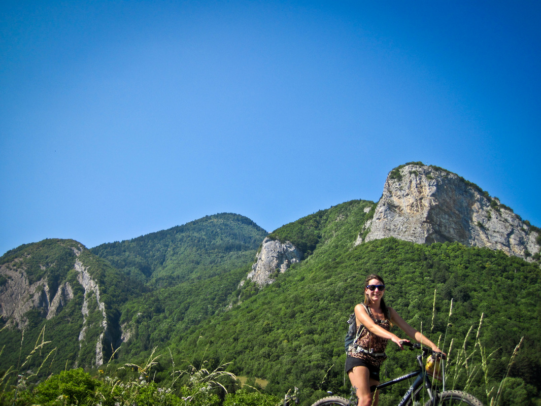 young woman smiling for a photograph on a bicycle in the foreground of the huge limestone outcrops of rock amongst the green wooded hillsides of the french alps near lake annecy.