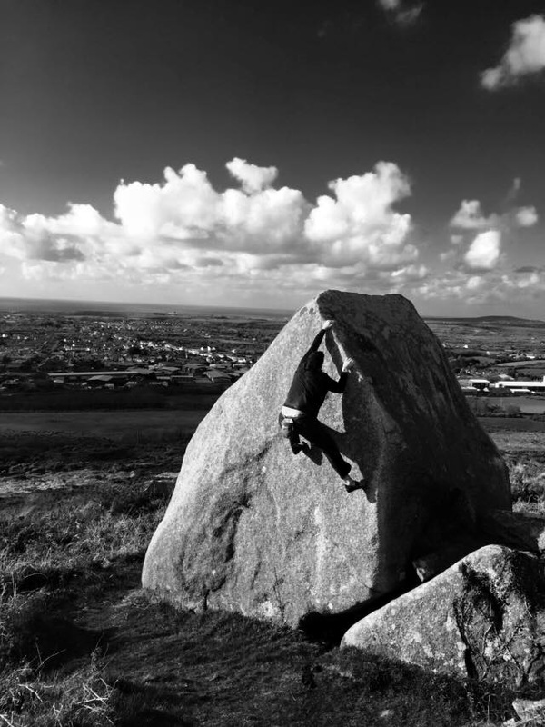 Pat climbing the classic arete at carn brea in black and white, GB bouldering