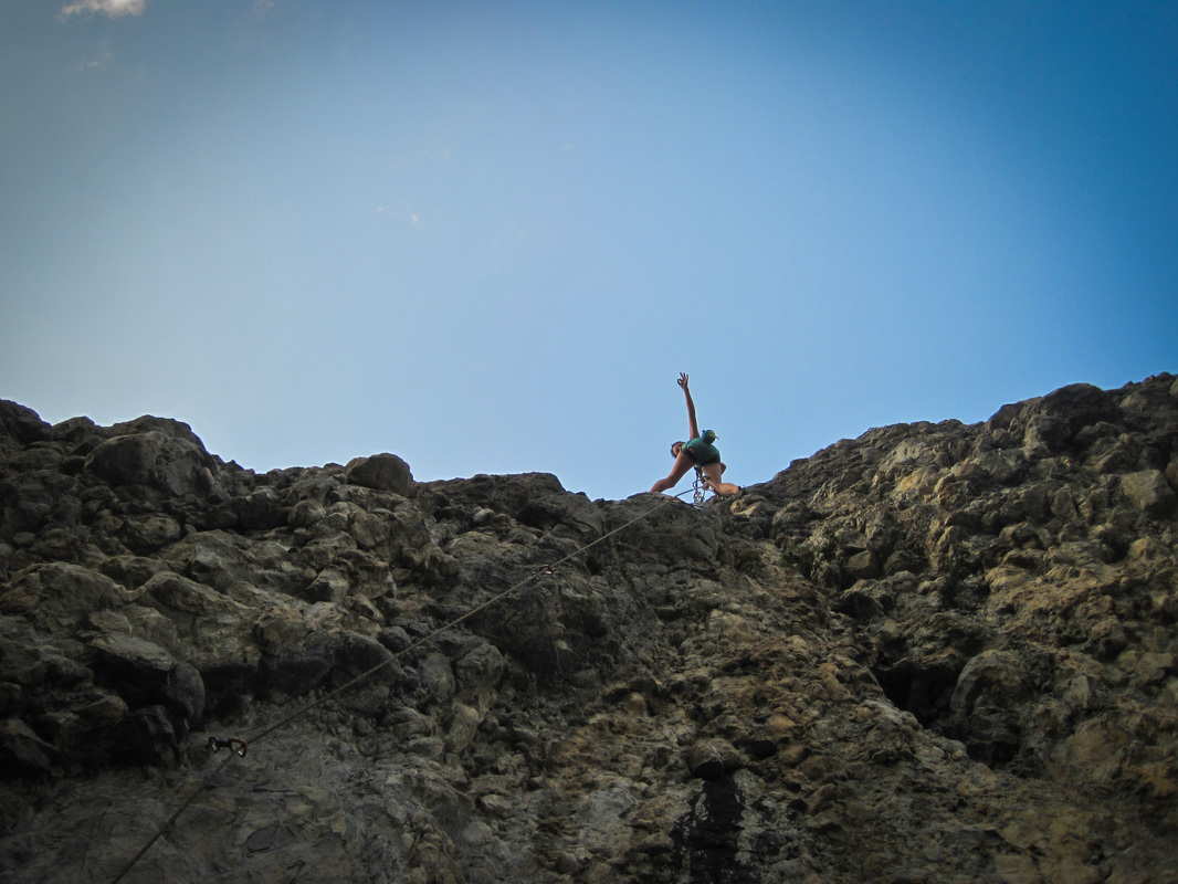 A young woman celebrating at the top of a hard rock climb in savines-le-lac with a blue sky backdrop