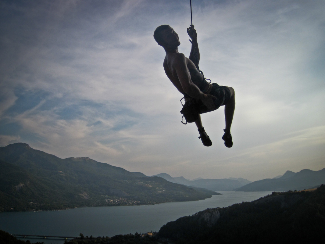 A young man dangling from a climbing rope on the decent of a rock climb with the lac du serre poncon and the surrounding mountains in the background