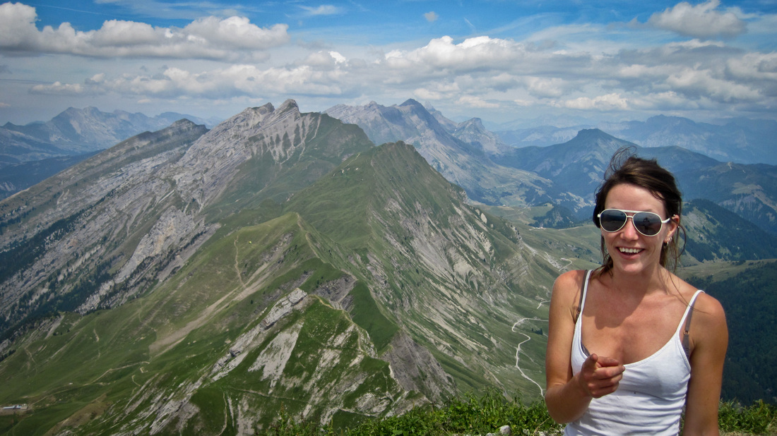 young woman posing for a camera on the summit of a mountain with more mountains in the background