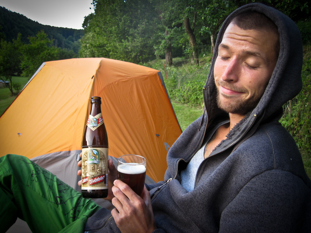 Man sitting next to an orange Marmot fuse 2p tent drinking bavarian beer
