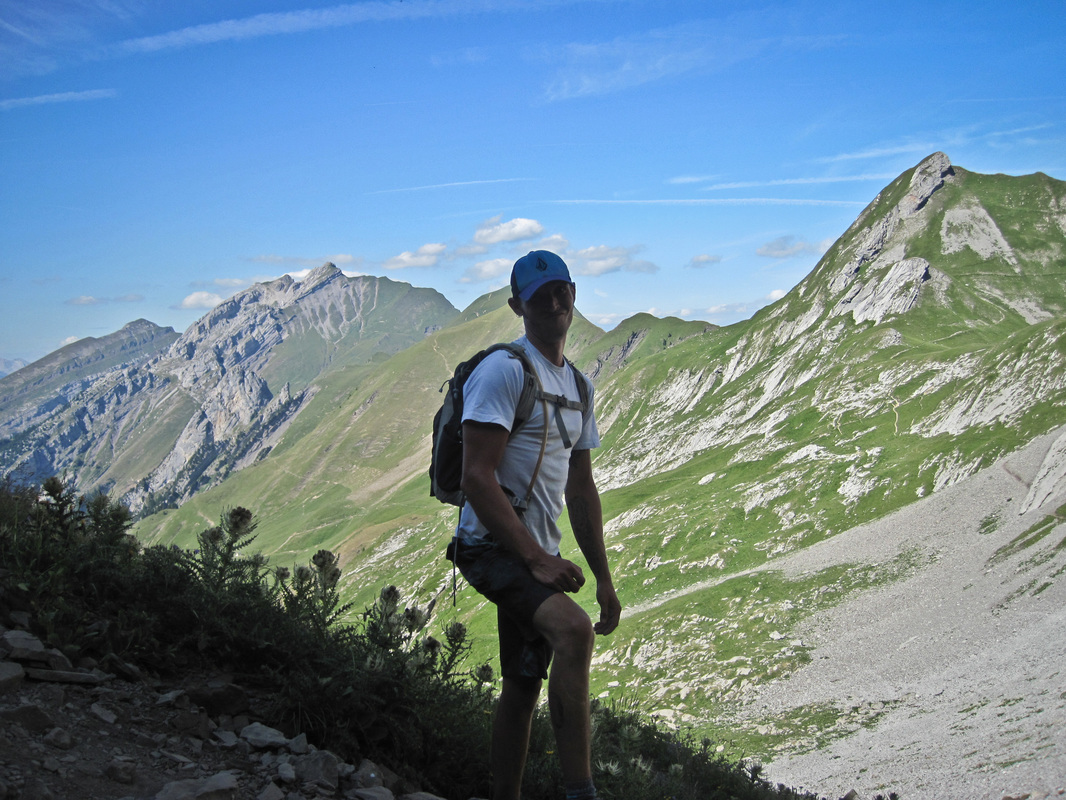 Young man on the walking descent of a mountain posing for a camera, mountains surrounding the scene