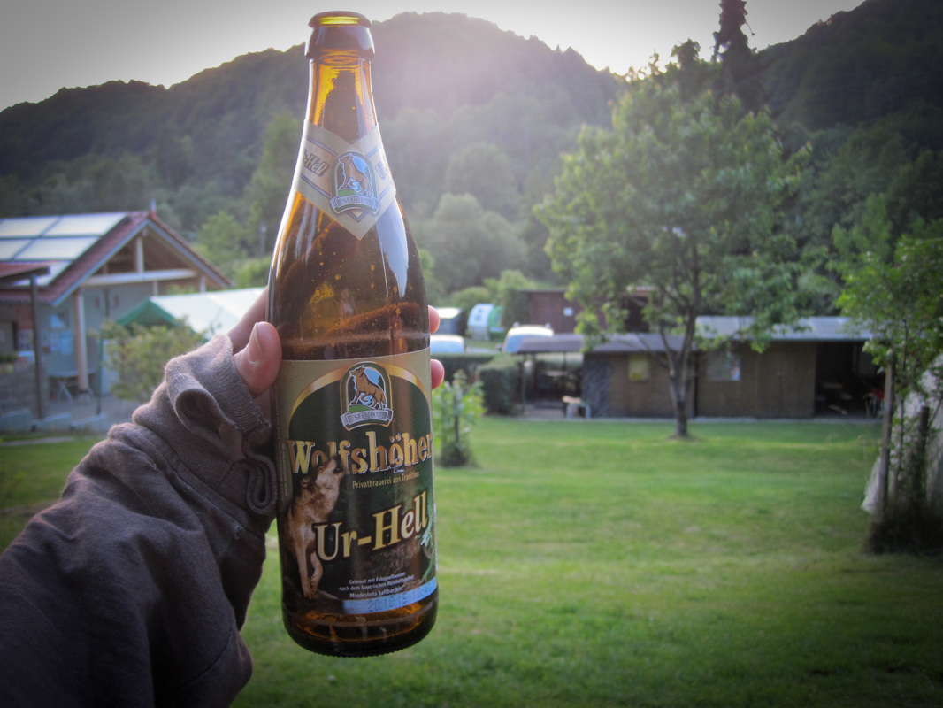 hand holding up an Ur-Hell bavarian beer with the Gasthof Eichler in the background