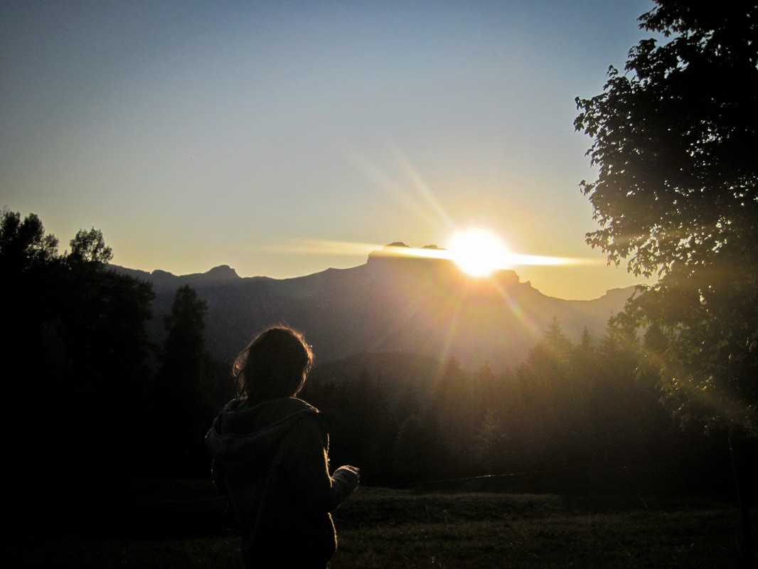 Sun setting over a mountain ridge with the silhouettes in the foreground of a young woman and trees.