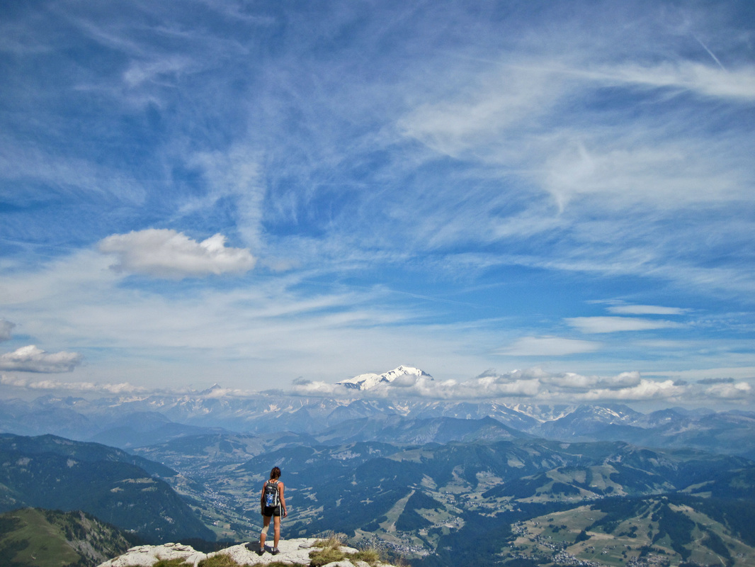 Young woman stands on the edge of the peak of Mont Charvin in the french alps looking across the vast mountainous terrain towards Mont Blanc and the snowcapped mountain massif on clear sunny day