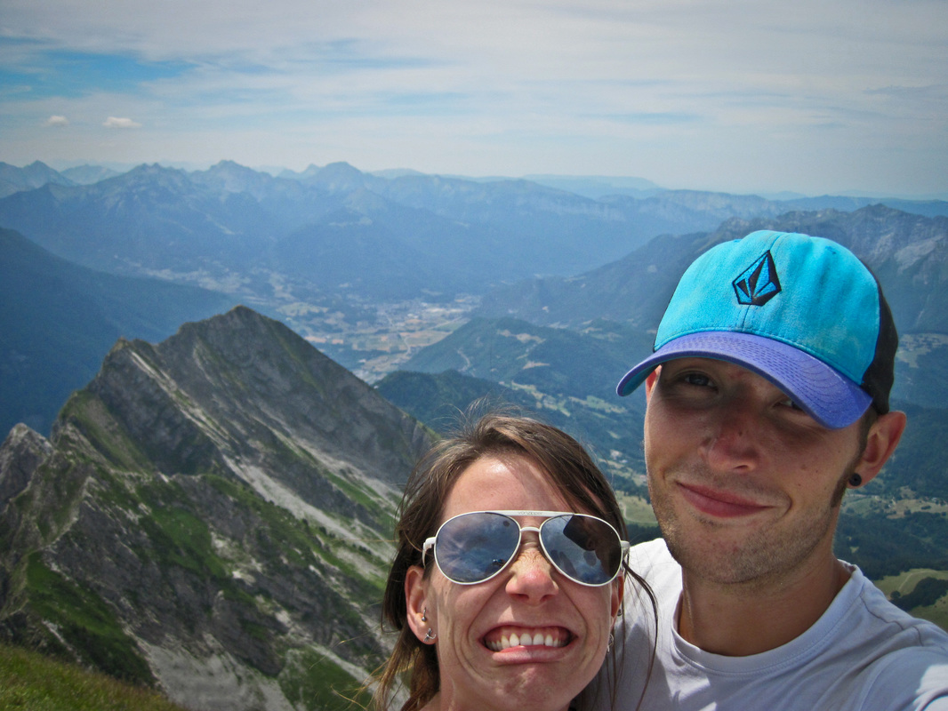 young man and woman posing for a camera on the summit of a mountain with more mountains in the background