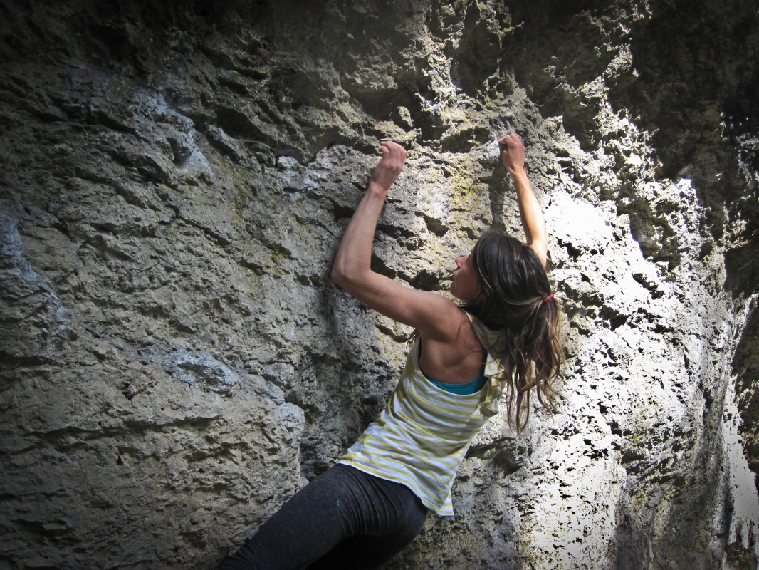 female rock climber hanging on by fingertips on rock in the frankenjura, germany