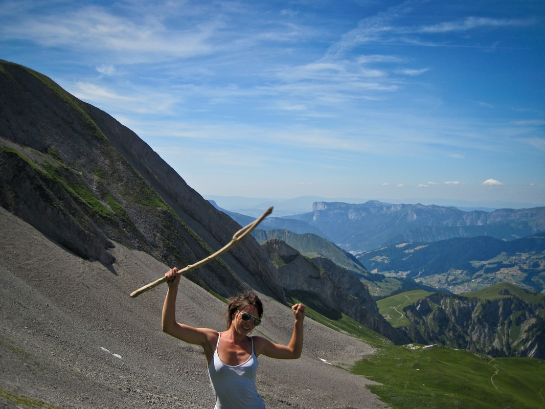 Young woman on the walking descent of a mountain posing for a camera by waving a stick in the air, mountains surrounding the scene